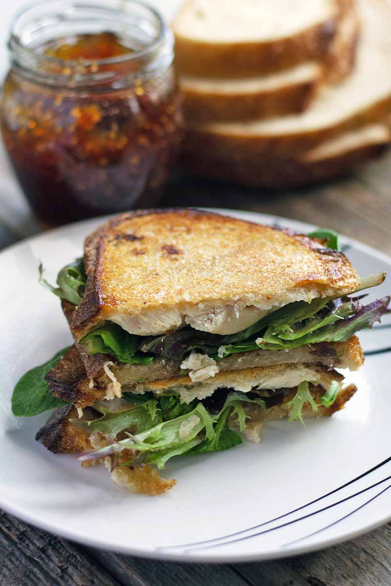 Vertical image of a chicken panini, sliced in half with the pieces stacked on top of each other on a white plate, with a stack of untoasted bread and a jar of fig jam in the background.