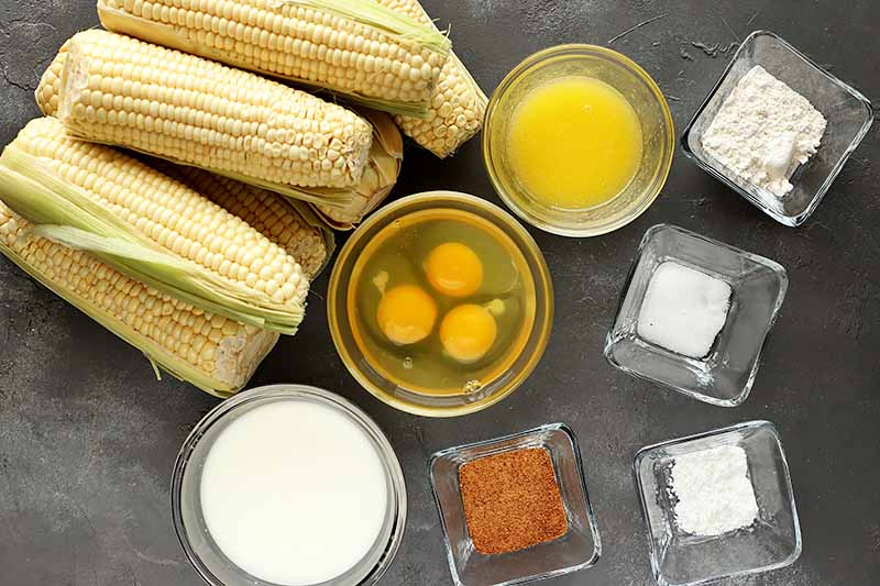 Horizontal image of assorted measured ingredients in bowls and whole fresh corn.