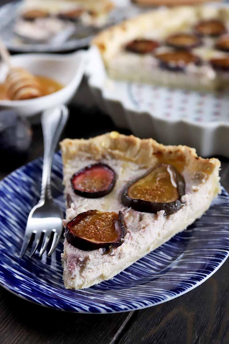 Vertical image of a slice of fig and ricotta tart on a blue plate with a fork, with a ceramic dish of honey with a wooden dipper in it and a white ceramic tart pan filled with the remaining dessert in the background.