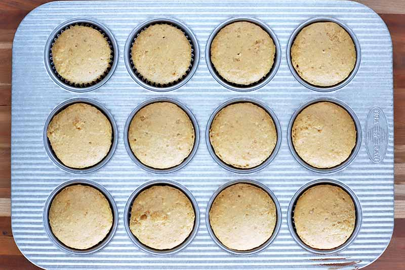 Horizontal overhead image of a metal tin of twelve homemade muffins on a brown wood surface.