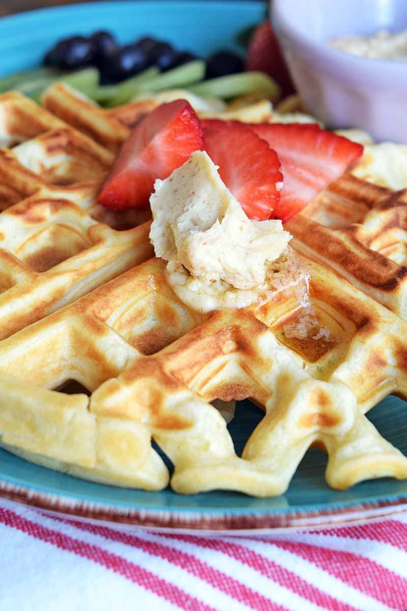 Vertical close-up image of a golden-brown waffle topped with strawberries and butter.