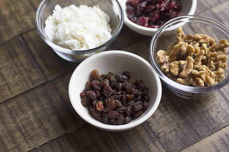 Horizontal image of dried fruit and nuts in small bowls.