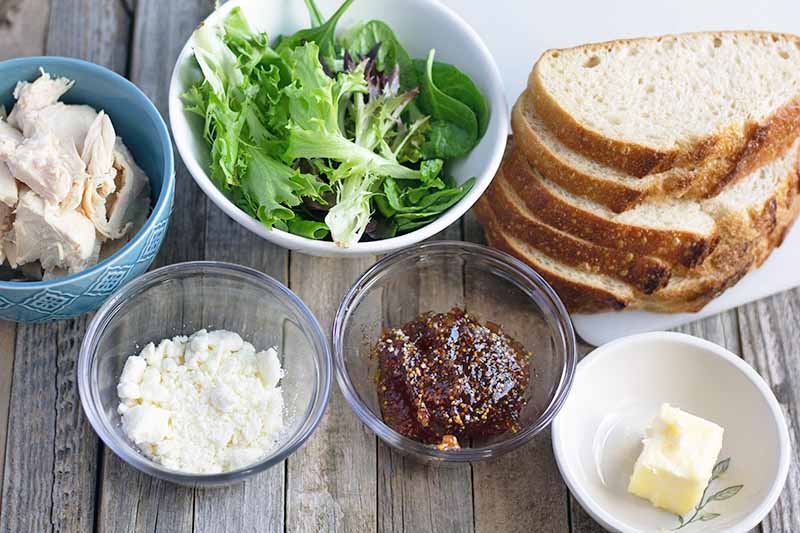 Horizontal image of two small glass, one small ceramic, and two slightly larger ceramic bowls of crumbled goat cheese, fig jam, butter, pieces of roasted chicken breast, and mixed salad greens, and a small pile of sliced sourdough bread, on an unfinished wood surface with a piece of parchment at the top right of the frame.