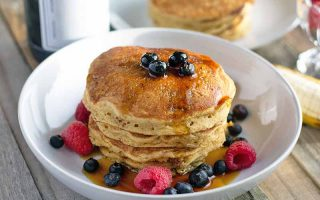 Horizontal image of a stack of pancakes in a shallow white ceramic bowl, with syrup and fresh berries, and another plate of flapjacks in the background, on an unfinished wood table.
