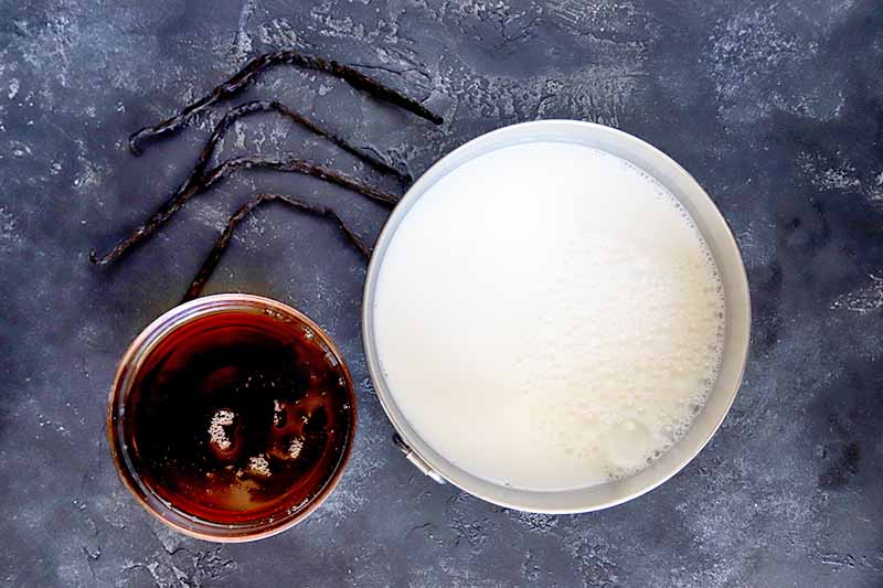 Horizontal overhead image of a stainless steel bowl of milk, a smaller glass bowl of maple syrup, and four whole vanilla beans with a bend in the middle, on a gray and white mottled surface.