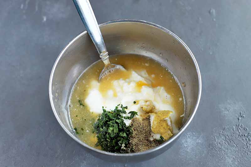 Horizontal overhead image of a stainless steel bowl of yogurt, orange juice, chopped green herbs, and spices, with a spoon for stirring, on a gray surface.