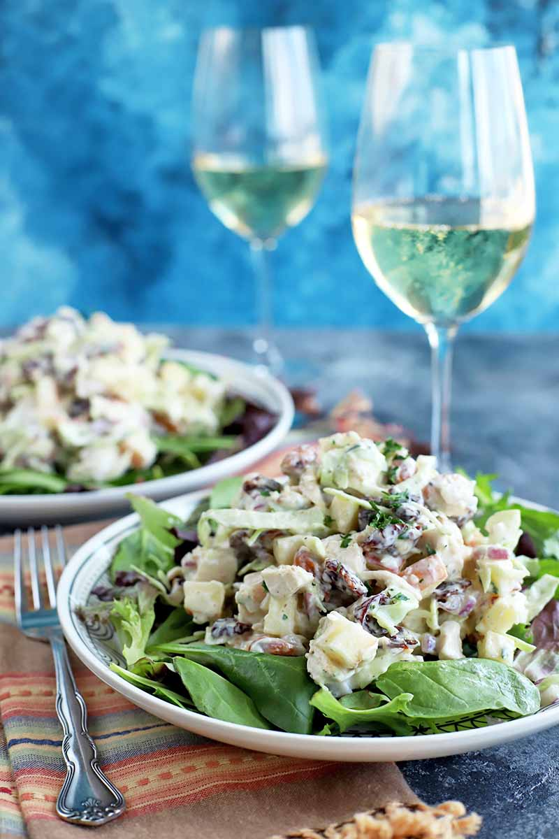 Vertical image of two white plates of salad greens topped with chicken salad, with a striped folded cloth napkin and a fork, and two glasses of white wine, on a gray surface with a mottled blue background.