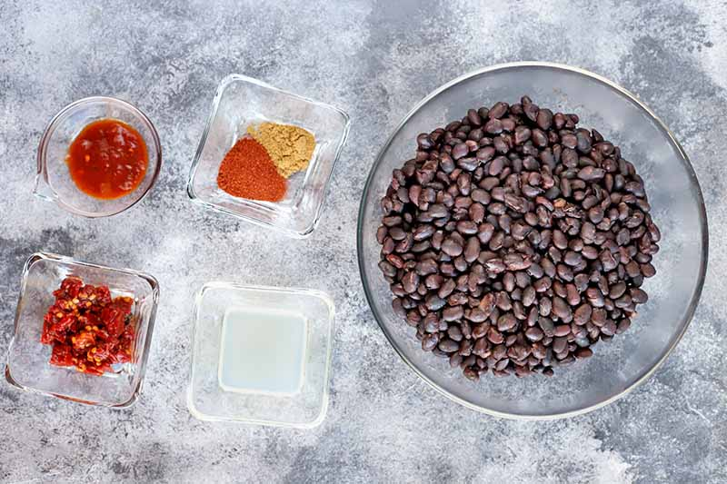 Overhead image of three small glass dishes of chipotles in adobo, spices, and lime juice, with a larger glass bowl of black beans to the right, on a mottled white and blue-gray surface.