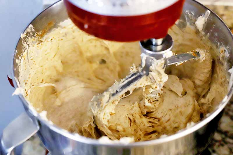 Closely cropped horizontal image of a red stand mixer beating a creamy yellow mixture in a stainless steel bowl with a paddle attachment.