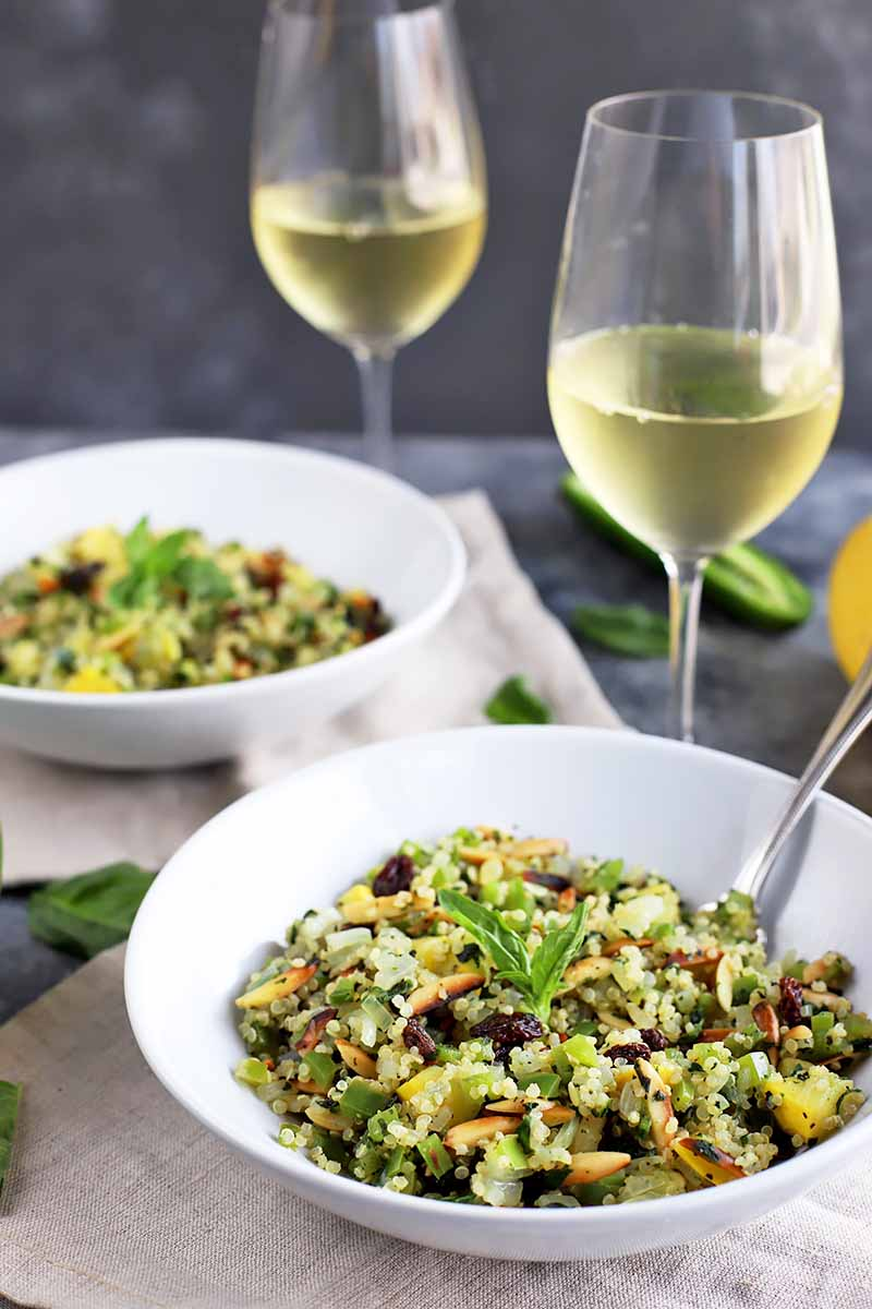 Vertical image of a quinoa and vegetable side dish in two white bowls next to glasses of white wine and basil leaves.