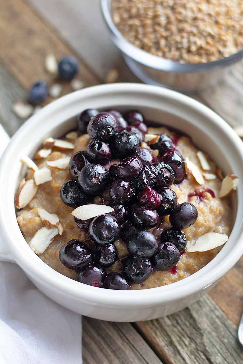 Vertical oblique overhead image of einkorn porridge with slivered almonds and roasted blueberries on top, on an unfinished wood surface with a small glass dish of uncooked grain and a white cloth, and a few scattered topping ingredients.