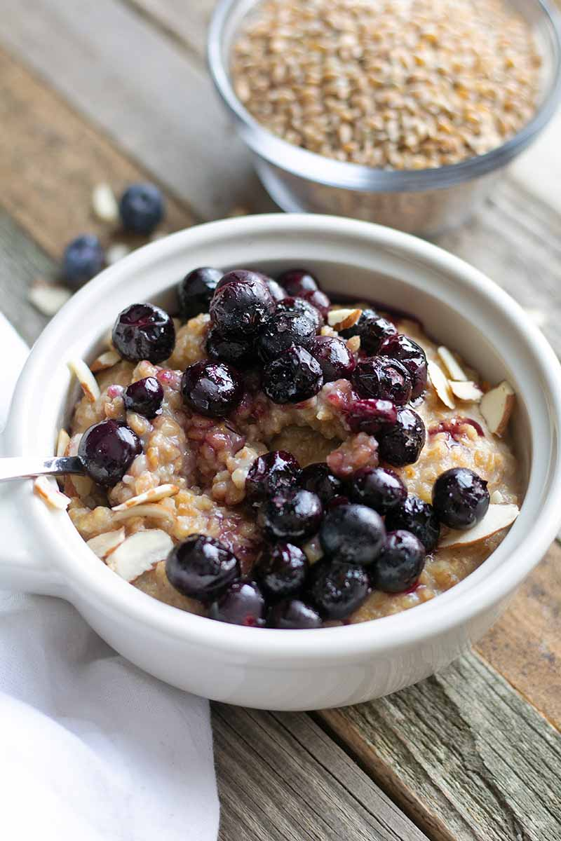 Vertical oblique overhead image of a white ceramic dish of einkorn porridge topped with roasted blueberries, with a small clear glass dish of the raw grain, a white cloth, and a few scattered pieces of fruit and slivered almonds on an unfinished wood surface.