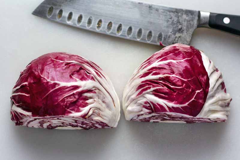 Horizontal overhead image of a small head of purple and white radicchio that has been cut in half, with the two pieces arranged side by side cut side down on a white plastic cutting board, with a santoku knife at the top of the frame.