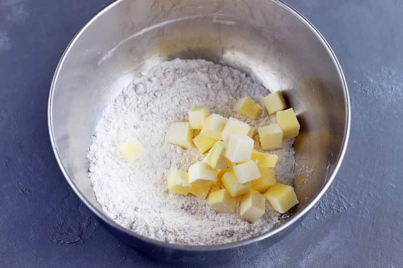Horizontal closely cropped overhead image of a metal mixing bowl of flour and cubed butter, on a gray surface.