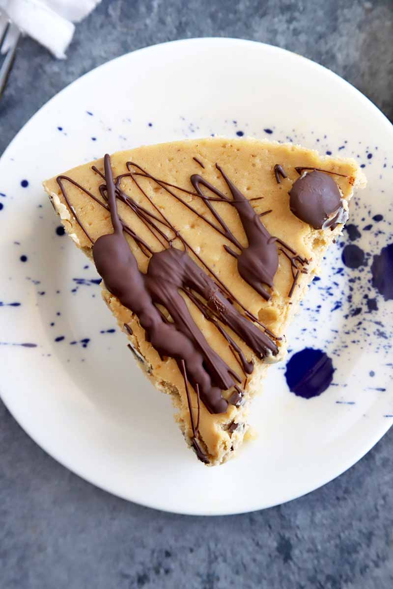 Vertical overhead image of a white plate with blue speckles with a slice of cheesecake on top, garnished with a chocolate drizzle, on a gray surface.