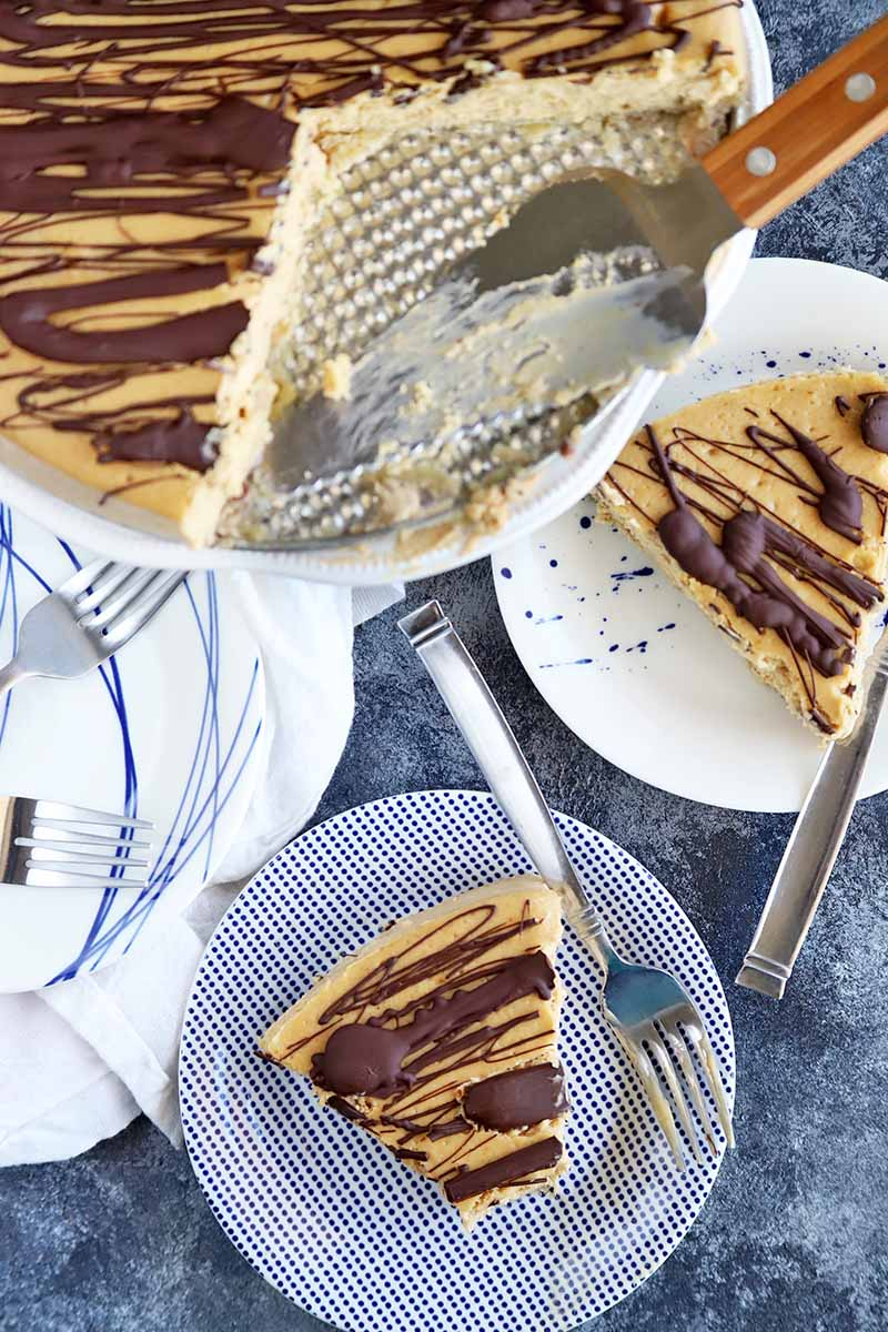 Vertical overhead image of two plates topped with slices of cheesecake with a chocolate drizzle on top and forks on the rims of each dish, with more plates and cutlery on a white cloth to the left, and the remainder of the dessert on a cake stand with a serving utensil at the top of the frame, on a blue-gray and white mottled surface.