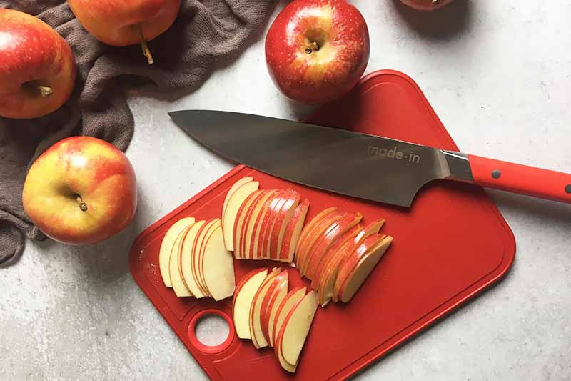 Horizontal image of a sliced apples and a knife on a red cutting board.