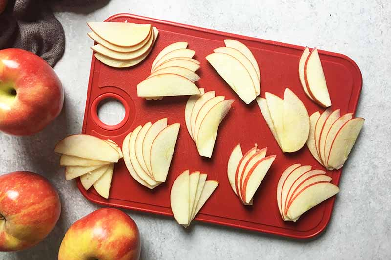 Horizontal image of assorted fanned out apple slices on a red cutting board.