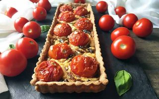 Horizontal image of a whole rectangular tomato tart on a dark slate surrounded by tomatoes, basil, and a white napkin.