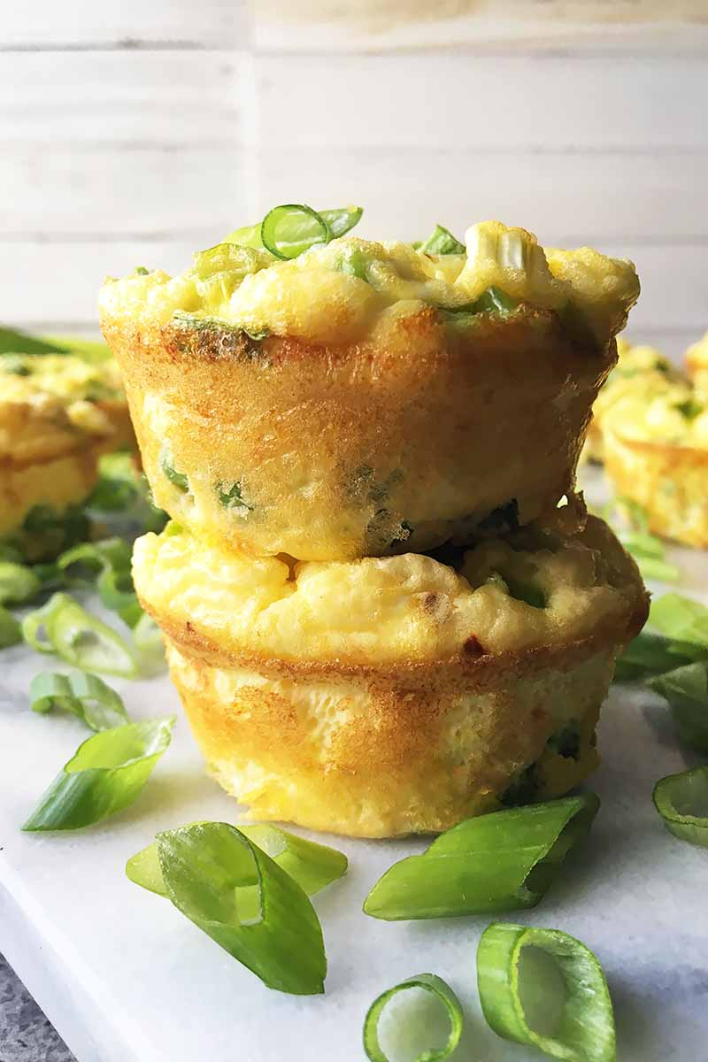 Vertical image of a stack of egg muffins with sliced scallions.