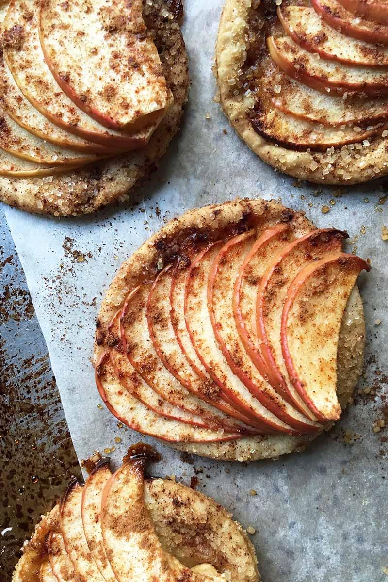 Vertical image of baked mini apple tartlets.