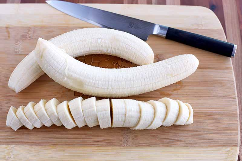 Horizontal image of two peeled one one sliced banana on a wooden cutting board with a knife.