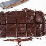 Horizontal image of squares of brownies next to a knife.