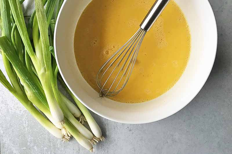 Horizontal image of a large white bowl with a deep yellow liquid and a whisk, next to a bunch of scallions.