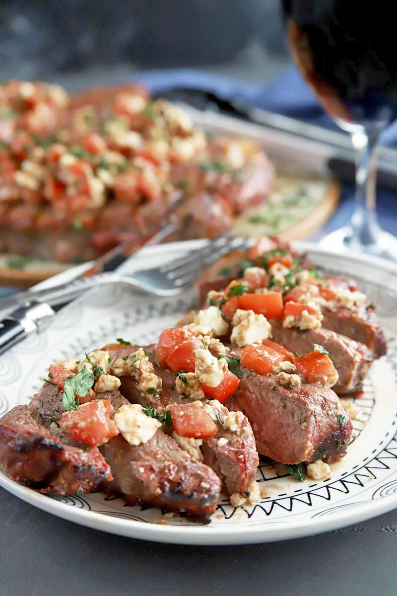 Vertical image of a black and white plate of steak topped with herbs, feta, and chopped tomato in the foreground with a serving platter containing more beef in soft focus in the background, with silverware and a glass of red wine on a gray surface.