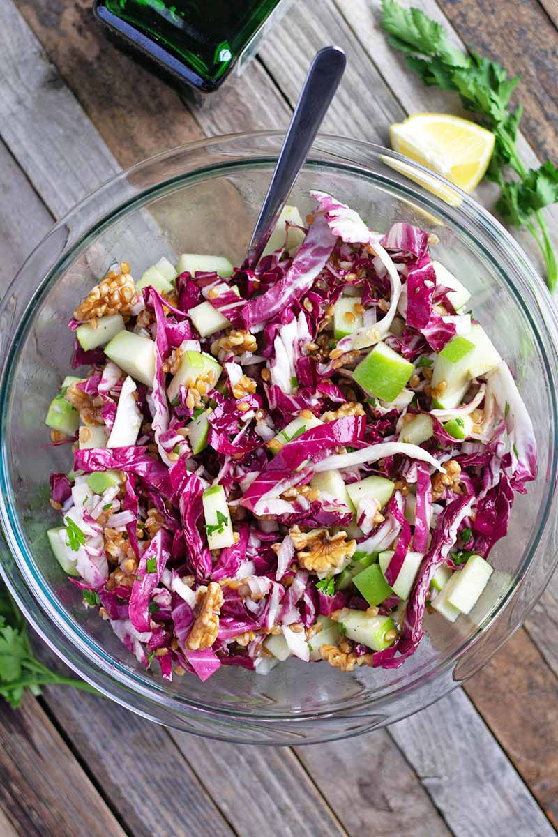 Overhead vertical image of a glass of einkorn, green apple, radicchio, and walnut salad, with a spoon stuck into the bowl, a green bottle of oil, sprigs of green Italian flat leaf parsley, and lemon wedges, on an unfinished wood table.