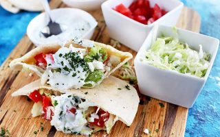 Hoizontal image of two Greek-style chicken pitas with fresh vegetables, herbs, and a white sauce, on a wooden cutting board with round and square dishes of various sizes filling with extra topping ingredients, on a blue cloth surface.