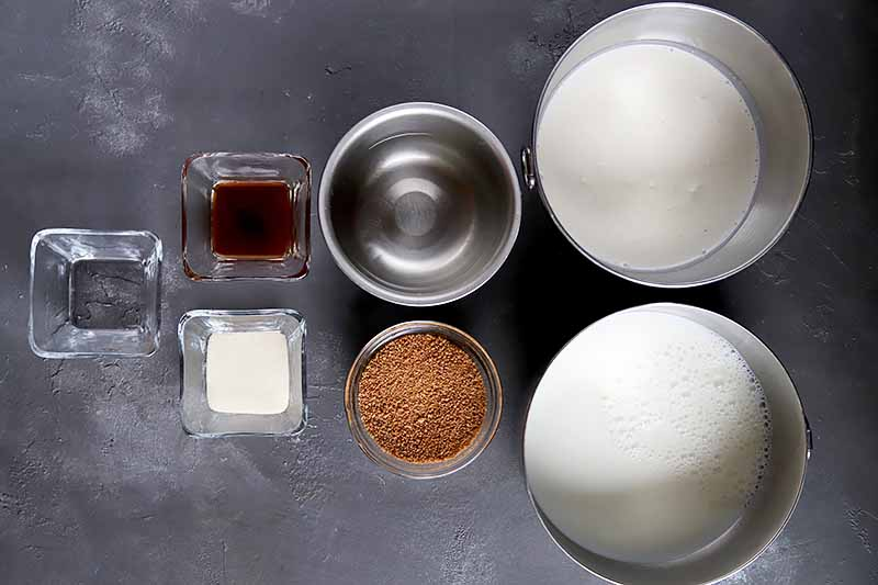 Horizontal image of assorted ingredients in glass and metal bowls on a dark gray surface.