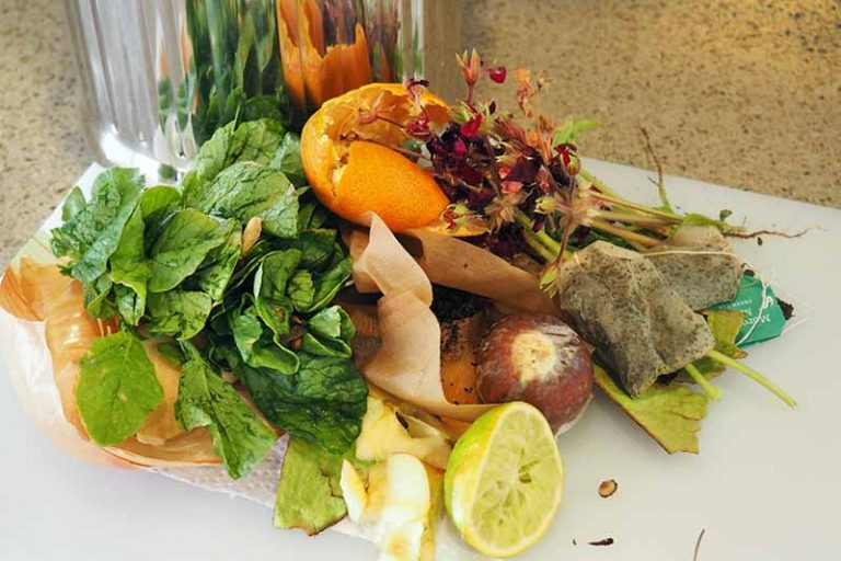 Horizontal head-on image of a pile of wilted flowers, citrus peels, greens, used teabags, and other forms of kitchen waste on a white plastic cutting board, with a stainless steel pail for collection in the background, on a beige countertop.