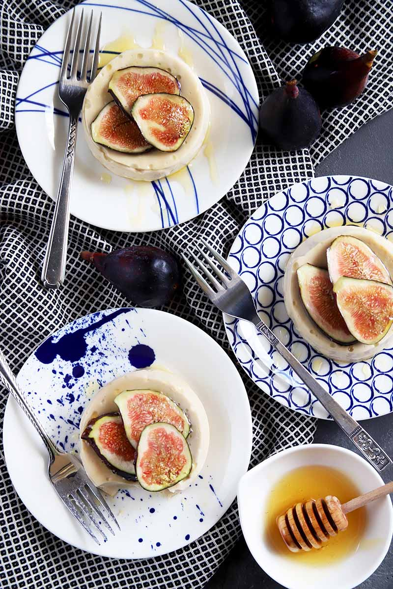 Vertical top-down image of three plates with desserts topped with figs, next to napkins, forks, and honey.