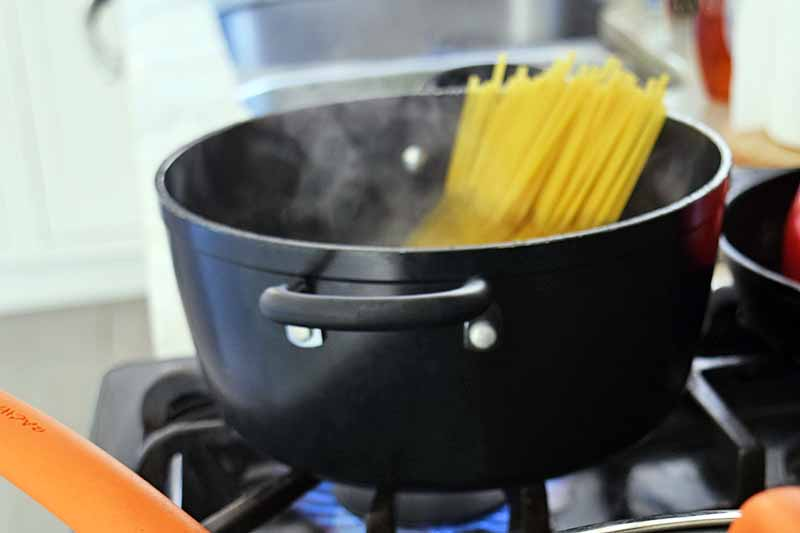 Horizontal image of raw noodles that have just been added to a black nonstick pot of boiling water on a gas stove.