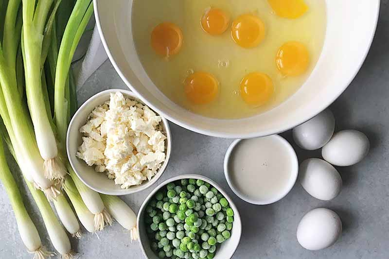 Horizontal image of a large bowl with whole eggs, and other small bowls with feta, peas, and milk.
