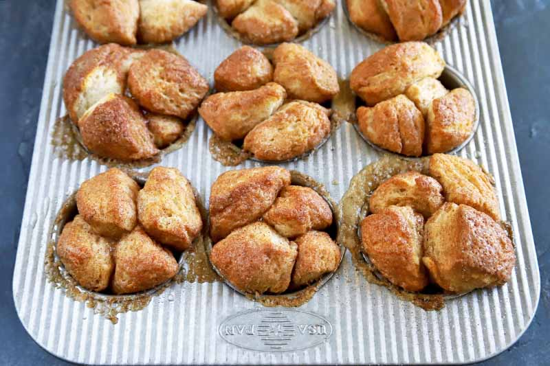 Horizontal oblique overhead image of a metal baking pan of monkey bread muffins topped with a combination of cinnamon and sugar, on a blue-gray background.