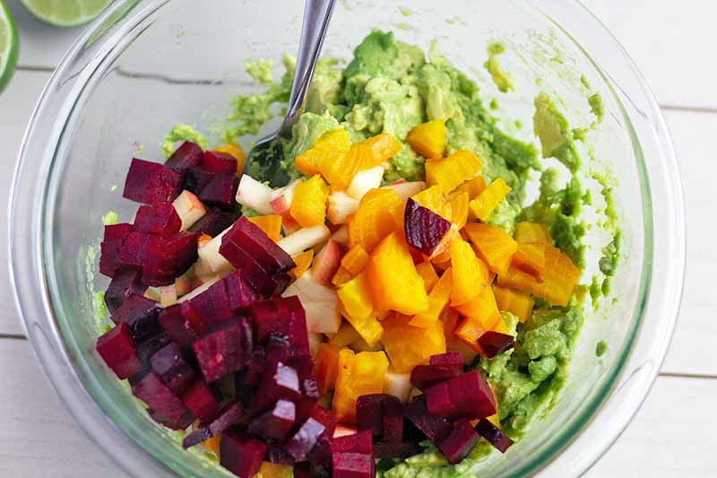 Overhead horizontal image of mashed avocado in a glass bowl with a spoon, topped with diced roasted purple and golden beets and chopped apple, on a white wood surface with sliced fresh lime at the top left corner of the frame.