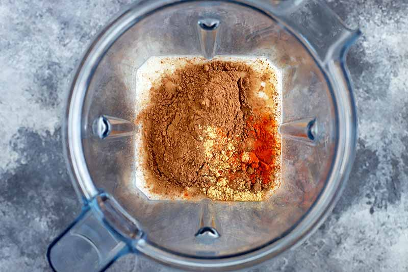 Horizontal overhead image of a clear plastic high-speed blender pitcher with a combination of milk, cocoa powder, powdered ginger, and cayenne powder at the bottom, on a gray sponge-painted surface.