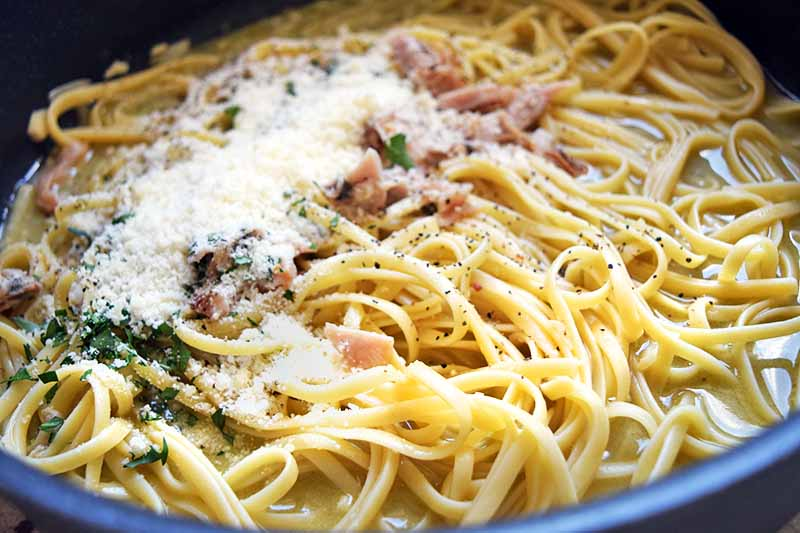 Horizontal image of grated cheese, chopped herbs, and cooked clams on cooked linguine in a large frying pan.