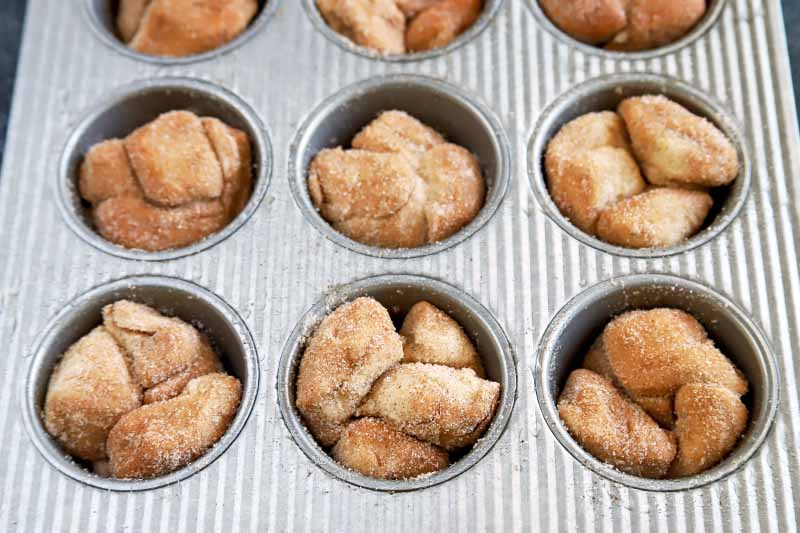 Horizontal nearly overhead image of chunks of biscuit dough coated with cinnamon and sugar, filling the wells of a metal muffin pan.
