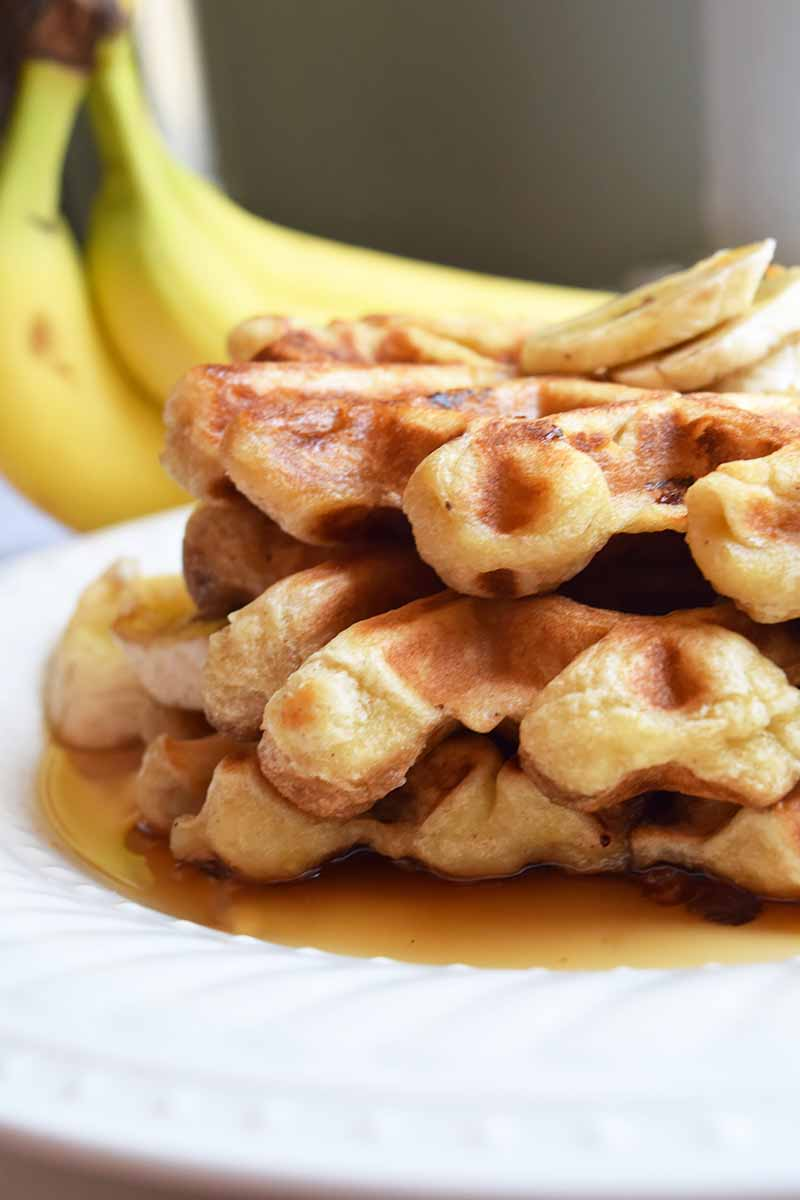 Vertical image of a stack of fluffy waffles in syrup with bananas in the background.