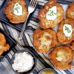 Horizontal overhead image of German potato pancakes on a white serving dish and two small, square black plates, with two forks, and small dishes of sour cream and applesauce, on a black, gray, and white striped cloth.