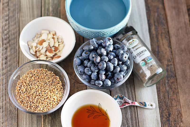 Overhead horizontal image of two white ceramic, two glass, and one light blue ceramic bowl of water, slivered almonds, einkorn berries, blueberries, and maple syrup, a small ceramic measuring spoon, and a glass jar of ground cardamom, on an unfinished wood surface.