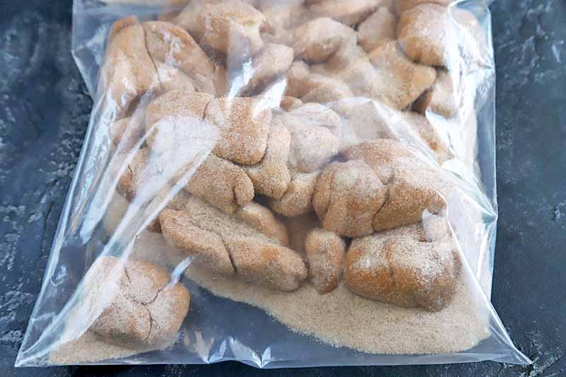 Horizontal overhead image of a clear plastic bag of bite-sized pieces of dough coated in a mixture of cinnamon and granulated sugar, on a blue-gray surface.