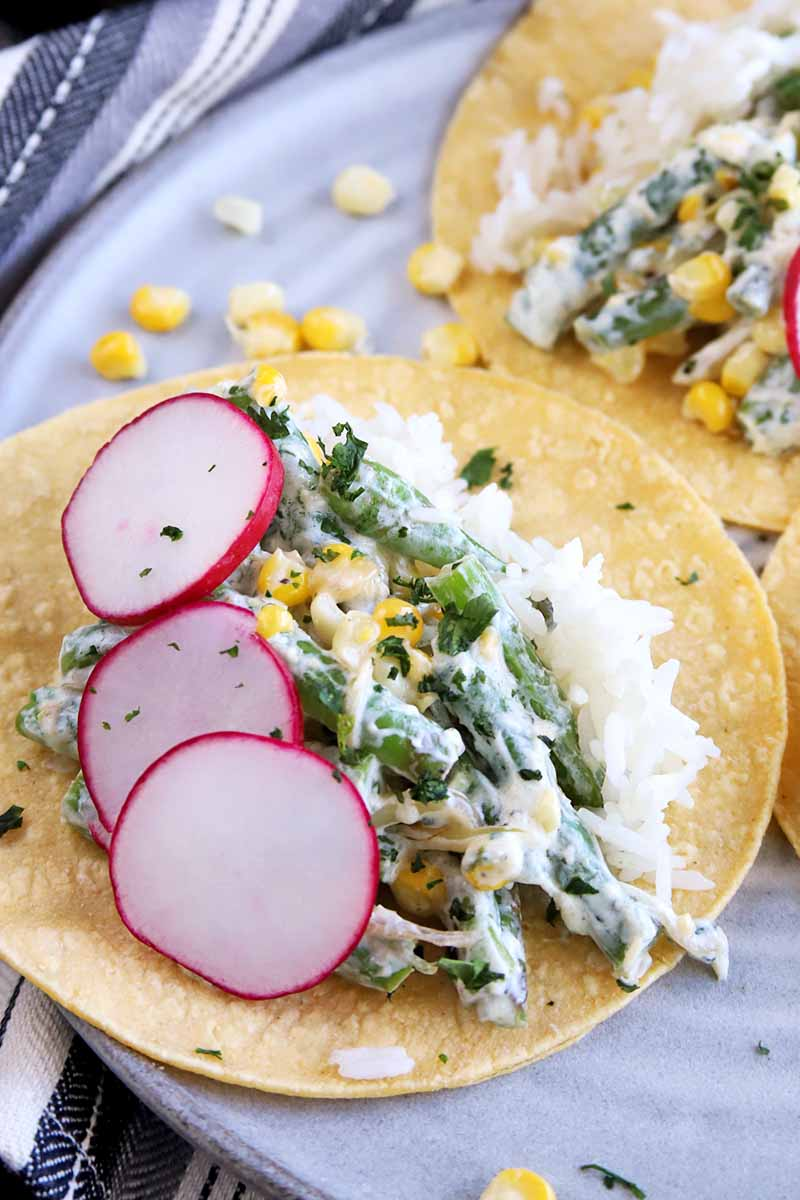 Vertical image of a green bean and corn filling coated with a white sauce and garnished with thinly sliced radish fills a yellow corn tortilla, on a plate with more tacos, on top of a gray striped cloth.