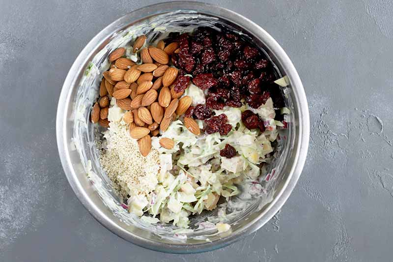 Horizontal overhead image of a stainless steel bowl of almonds, dried cherries, and other chicken salad ingredients, on a gray surface.