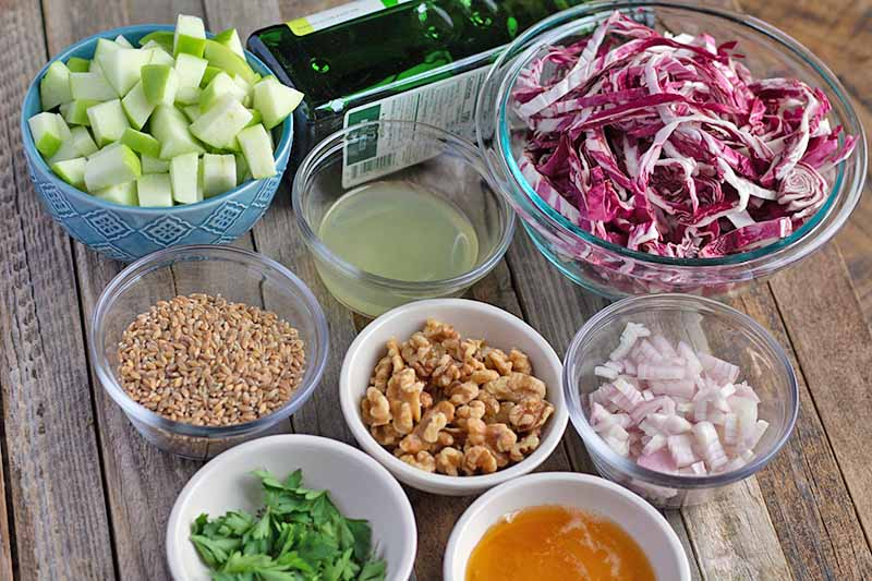 Oblique overhead horizontal image of eight medium-sized and small glass and blue or white ceramic bowls of chopped Granny Smith apple, lemon juice, shredded radicchio, walnuts, uncooked einkorn wheat, Italian parsley leaves, honey and chopped shallots, with a green bottle of olive oil that is resting on its side, on an unfinished wood table.