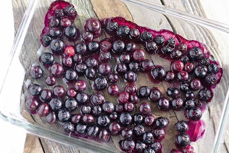 Horizontal overhead image of roasted blueberries in a clear glass baking dish, on an unfinished wood surface.