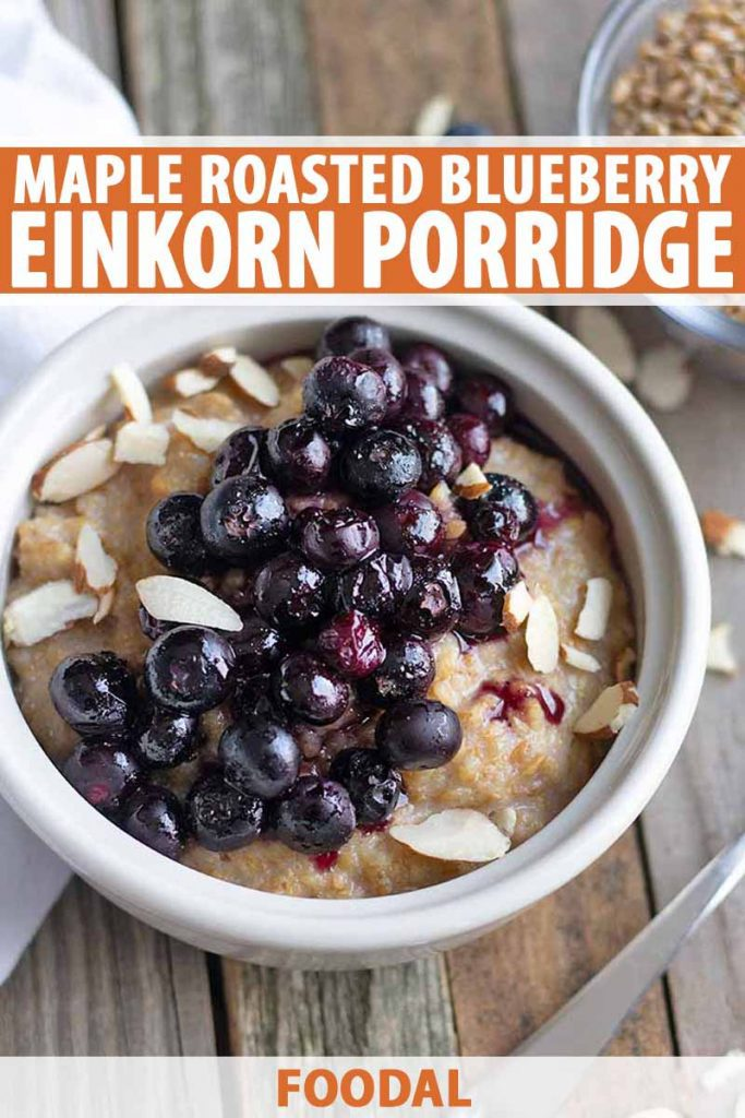 Overhead vertical image of a white dish of einkorn porridge topped with roasted blueberries, on an unfinished wood surface with a white cloth, a small bowl of grain, a spoon, and scattered slivered almonds, printed with white and orange text in the top third and at the bottom of the frame.
